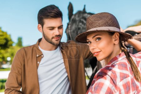 Photo for Beautiful equestrian standing near colleague and horse at ranch, looking at camera - Royalty Free Image