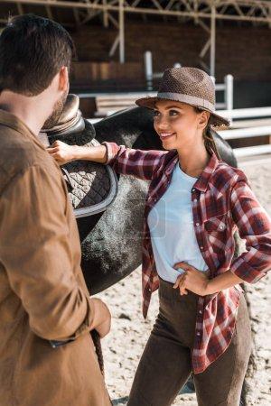Photo pour Jockeys debout près de cheval et de parler au ranch - image libre de droit