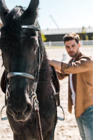 selective focus of handsome male equestrian fixing horse saddle at ranch