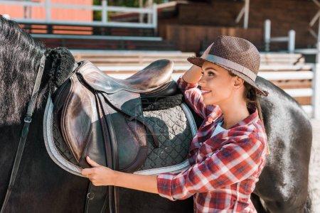 Photo pour Vue latérale du sourire attrayant féminin équestre fixation cheval selle au ranch - image libre de droit