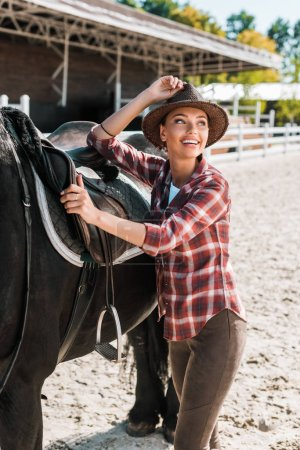 attractive smiling equestrian fixing horse saddle and touching hat at ranch