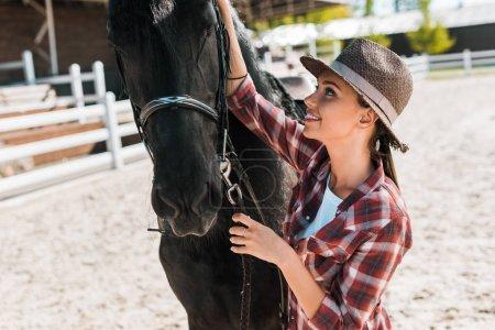 Photo pour Attrayant femme équestre en chemise à carreaux et chapeau fixation licol cheval au ranch - image libre de droit