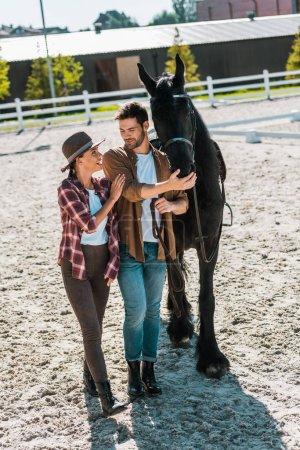 Photo pour Joyeux cavaliers mâles et femelles, marchant avec cheval au ranch - image libre de droit