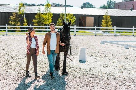 Photo pour Sourire de cow-boy et cow-girl dans des vêtements décontractés, marchant avec cheval au ranch - image libre de droit