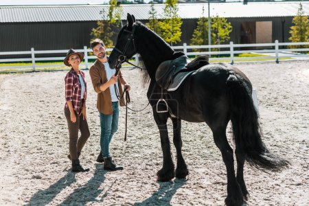 smiling female and male equestrians standing with horse at ranch