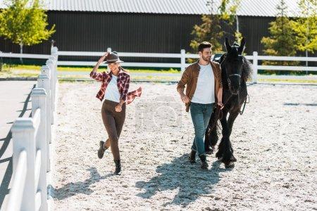 Photo pour Équestre male marchant avec cheval au ranch, heureux équestre féminin touchant chapeau - image libre de droit
