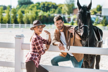 Photo pour Sourire de cowboy et cowgirl debout près de la clôture avec cheval au ranch - image libre de droit