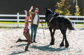 happy female and male equestrians walking with horse at ranch and waving hands