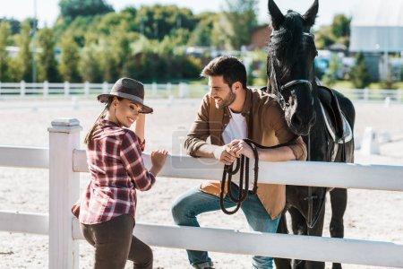 Photo pour Sourire de cowboy et cowgirl debout près de clôture avec cheval et parler au ranch - image libre de droit