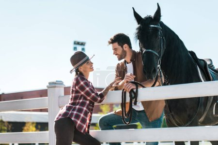 Photo for Smiling female and male equestrians standing near fence with horse and looking at each other at ranch - Royalty Free Image