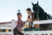 smiling female and male equestrians standing near fence with horse and looking at each other at ranch