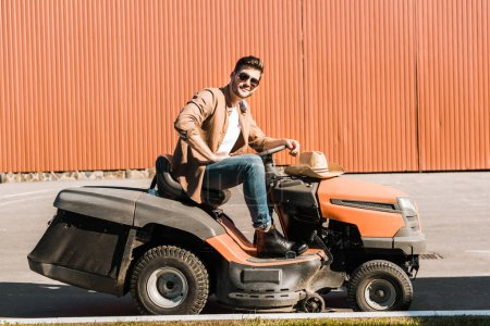 Photo for Handsome cowboy in casual clothes and sunglasses riding ranch vehicle near building - Royalty Free Image
