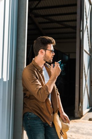 side view of handsome man in sunglasses smoking cigarette and leaning on wall at ranch