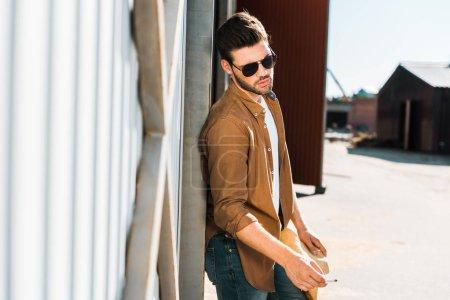 Photo pour Beau cowboy en lunettes de soleil tenant cigarette et s'appuyant sur le mur au ranch - image libre de droit