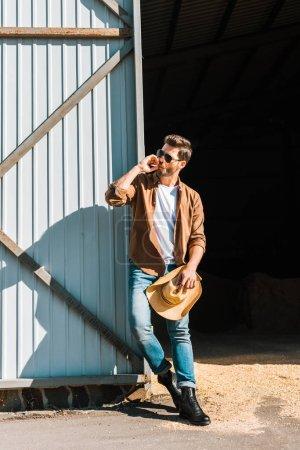 Photo pour Bel homme dans lunettes de soleil fumer cigarette, tenant le chapeau et s'appuyant sur le mur au ranch - image libre de droit