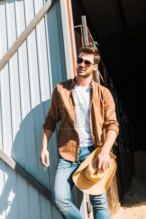 Photo pour Bel homme dans lunettes de soleil tenant la cigarette et chapeau, s'appuyant sur le mur au ranch - image libre de droit
