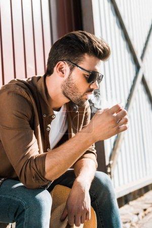 Photo pour Vue latérale du beau cowboy en lunettes de soleil assis et fumant cigarette au ranch - image libre de droit