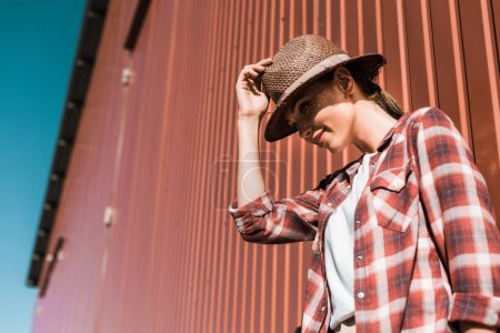 low angle view of attractive woman in checkered shirt and hat leaning on brown wall at ranch