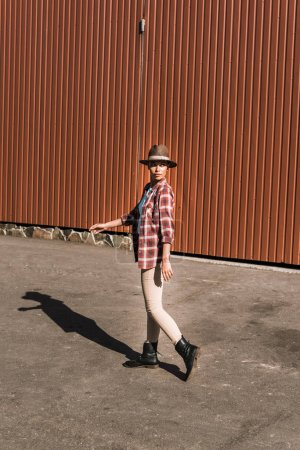 attractive cowgirl in checkered shirt and hat walking near brown building at ranch