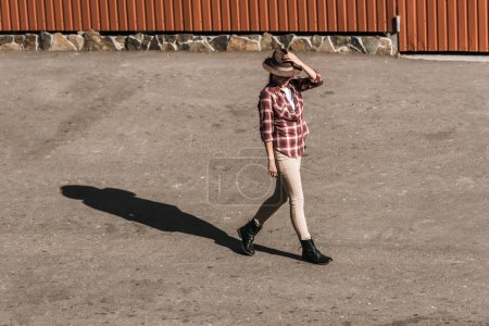 Foto de Mujer atractiva en camisa a cuadros tocando el sombrero y caminar cerca del edificio marrón en el Rancho - Imagen libre de derechos