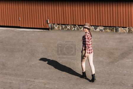 Foto de Vaquera atractiva sonriente en camisa a cuadros y sombrero caminando cerca del edificio marrón en el Rancho - Imagen libre de derechos
