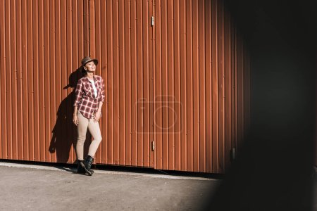 smiling attractive woman in checkered shirt and hat leaning on brown wall at ranch