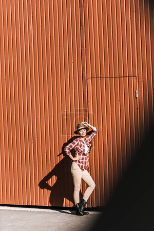 Photo for Smiling attractive cowgirl in checkered shirt touching hat and leaning on brown wall at ranch - Royalty Free Image
