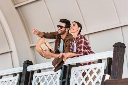 Photo pour Homme souriant pointant sur quelque chose à la femme de tribune au stade ranch - image libre de droit