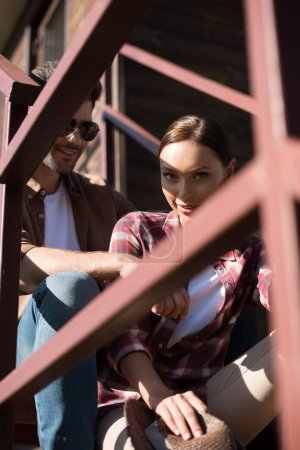 Photo for View through fence man and woman in casual clothes sitting on staircase at ranch - Royalty Free Image