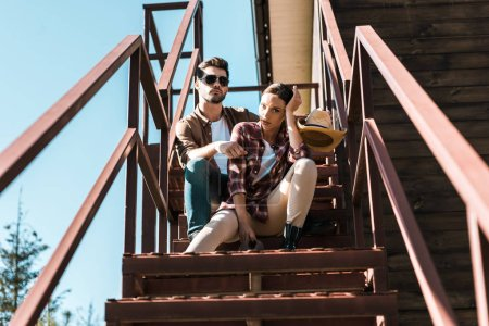 cowboy and cowgirl in casual clothes sitting on metal staircase at ranch