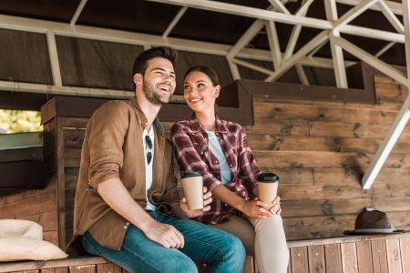 Photo pour Homme et femme assise avec des tasses à café jetables au ranch souriant - image libre de droit