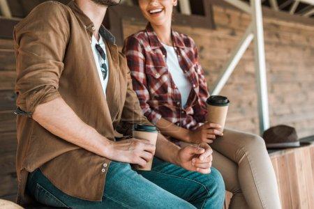 Photo pour Cropped image de cowboy et cowgirl assis avec des tasses à café jetables au ranch - image libre de droit