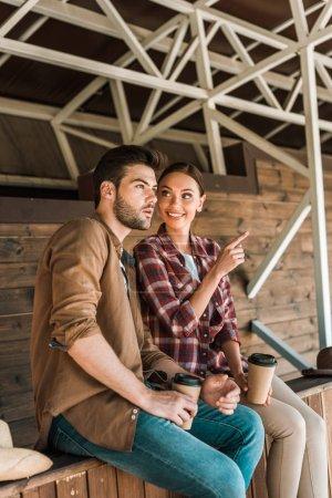 Photo pour Cowboy et cowgirl assis avec café pour aller au ranch, femme pointant sur quelque chose - image libre de droit