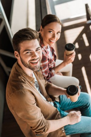 high angle view of smiling man and woman sitting with coffee to go at ranch and looking at camera