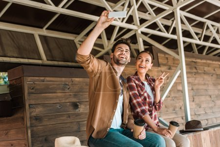 smiling cowboy and cowgirl taking selfie with smartphone at ranch