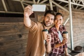 smiling man and woman taking selfie with smartphone and holding disposable coffee cups at ranch