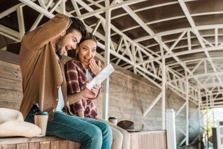 Photo pour Excité cowboy et cowgirl regardant comprimé au ranch - image libre de droit