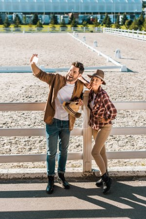 smiling stylish cowboy and cowgirl in casual clothes taking selfie with smartphone at ranch