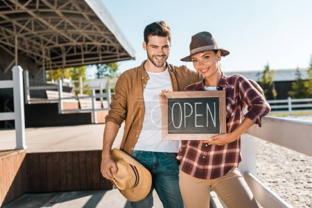 smiling stylish equestrians in casual clothes holding open sign at ranch and looking at camera