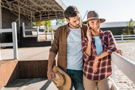 stylish cowboy and cowgirl in casual clothes standing near fence at ranch, woman talking by smartphone