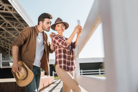 Photo for Selective focus of stylish equestrians in casual clothes taking selfie with smartphone at ranch - Royalty Free Image
