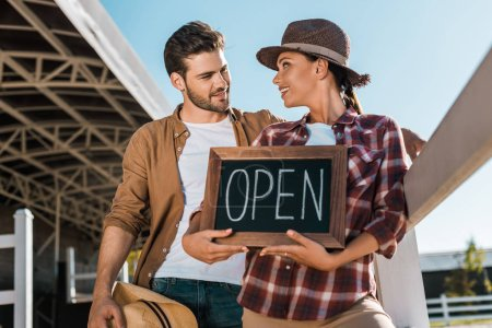 stylish cowboy and cowgirl in casual clothes holding open sign at ranch and looking at each other