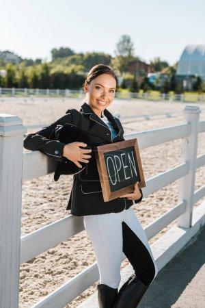 Photo pour Attrayante femme penchée équestre sur clôture et tenant ouvert signe au club cheval - image libre de droit