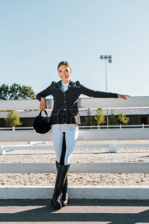 beautiful smiling female equestrian leaning on fence and looking at camera at horse club