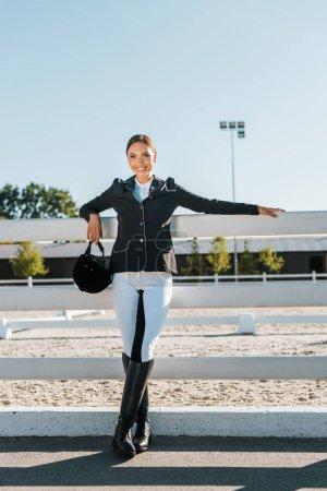 Foto de Bella sonriente mujer ecuestre que se inclina en cerca y mirando a cámara en el club del caballo - Imagen libre de derechos