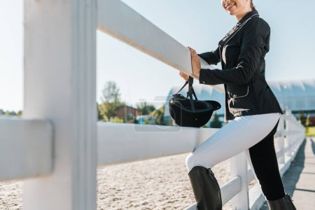 cropped image of smiling equestrian leaning on fence at horse club