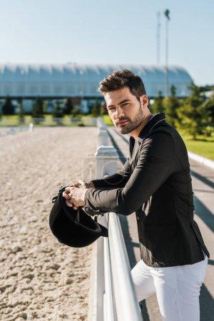 Photo pour Beau équestre en culotte blanche et veste noire, se penchant sur clôture avec casque d'équitation au club cheval - image libre de droit