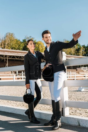 Photo for Handsome equestrian in professional apparel pointing on something to colleague at ranch - Royalty Free Image