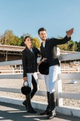 handsome equestrian in professional apparel pointing on something to colleague at ranch