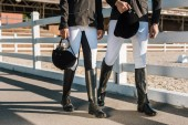 imagen recortada de jinetes profesionales ropa caminando junto a la valla y que cascos de montar a caballo en el Rancho